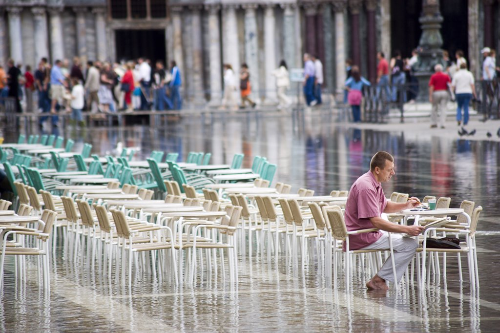 Italy, Veneto, Venice, Aqua Alta High Water Flooding In St Marks Square Showing St Marks Basilica At The End Of The Flooded Piazza With An Artist Painting A Watercolour Seated At A Table In The Water : Stock Photo