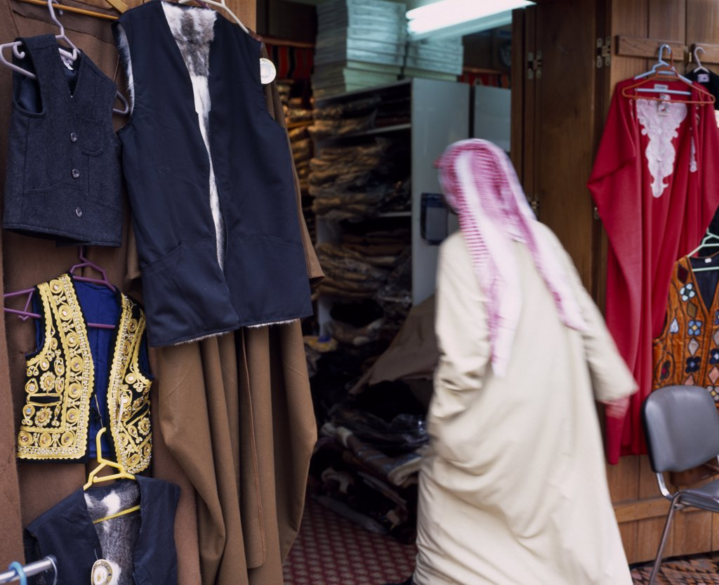 Stock Photo: 1850-19451 Kuwait, Kuwait City, Man In Dishdasha And Red And White Shmaaq Entering Clothes Shop In The Great Souq In Blurred Movement.