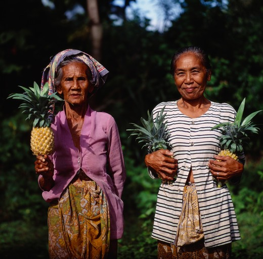 Stock Photo: 1850-1950 Indonesia, Lombok, Batu Layar, Two Ladies Near Senggigi Holding Pineapples