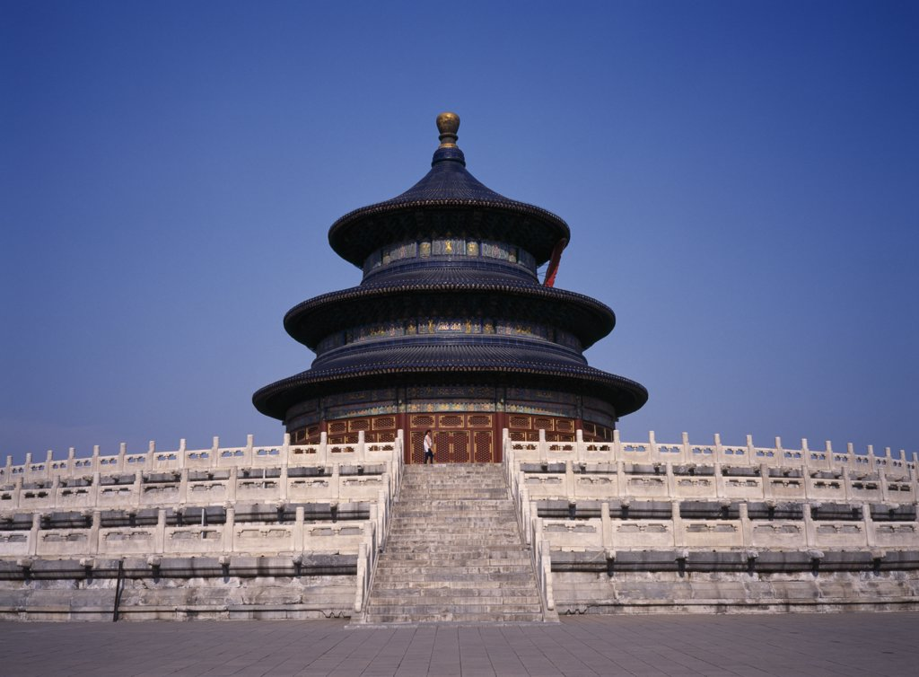 Stock Photo: 1850-19531 China, Beijing, Temple Of Heaven.  Hall Of Prayer For Good Harvests With Western Tourist Standing At Top Of Steps To Entrance.