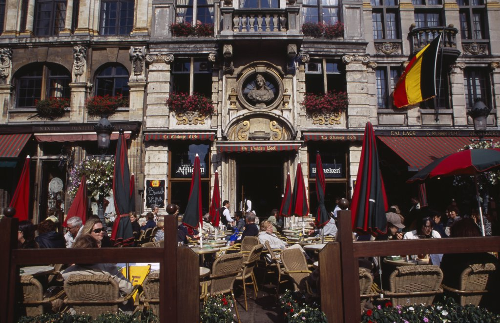 Belgium, Brabant, Brussels, Grand Place.  Busy Cafe With People Sitting At Outside Tables In The Sunshine.  Part View Of Building Facade With Stone Balcony And Flower Filled Window Boxes. Unesco World Heritage Site : Stock Photo