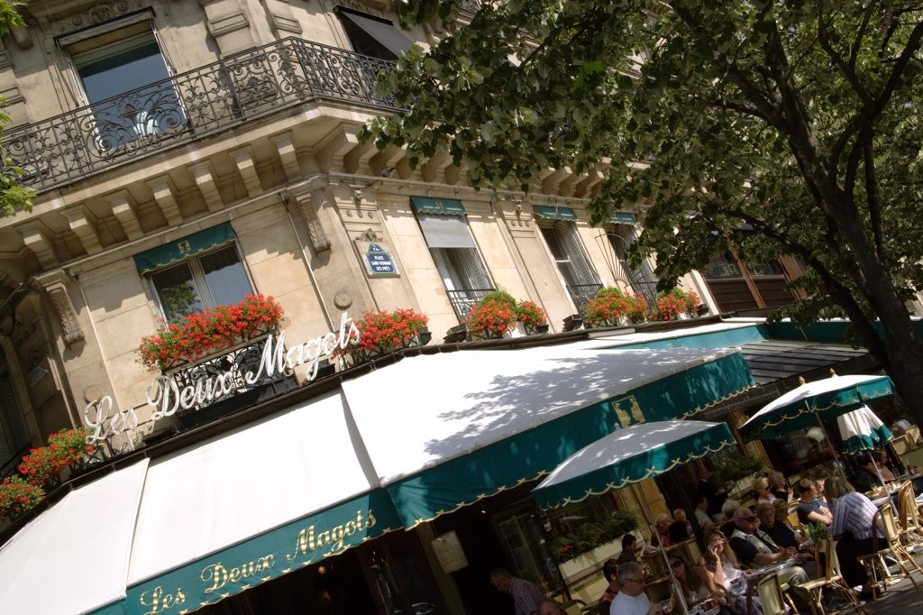 France, Ile De France, Paris, People At Pavement Tables Outside Les Deux Magots The Famous Literary Cafe Frequented By The Surrealists On Place St Germain Des Pres : Stock Photo
