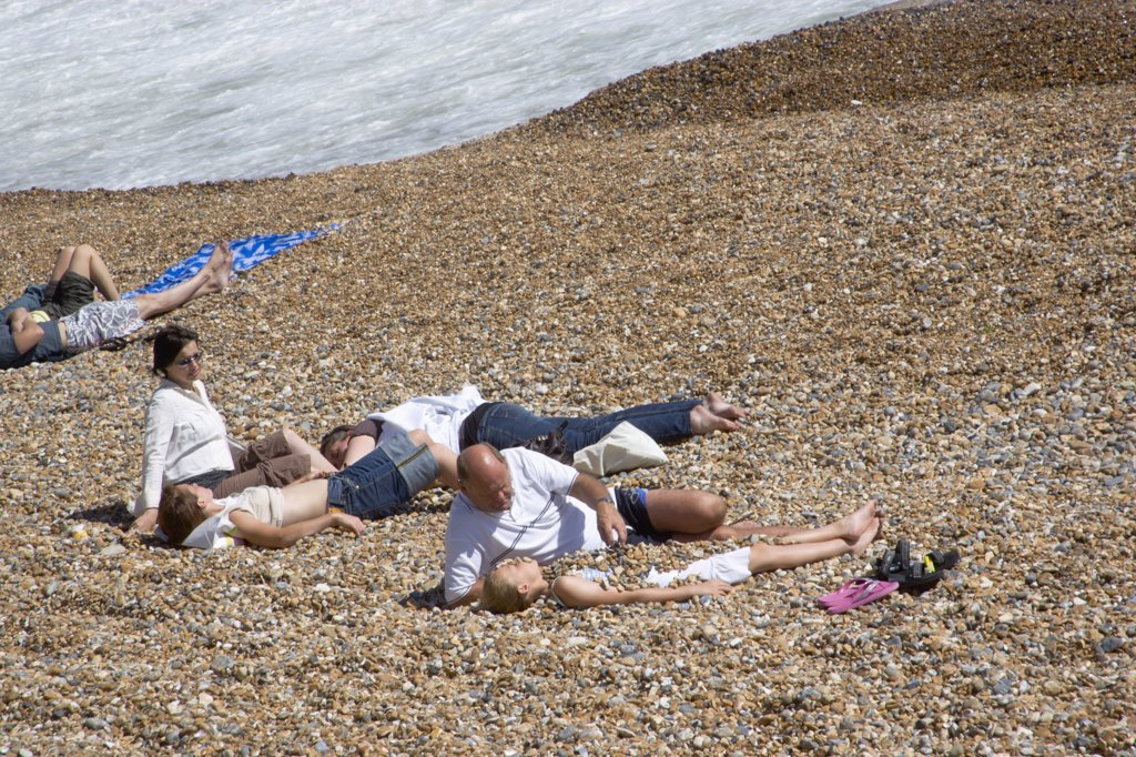 England, East Sussex, Brighton, Family On The Stoney Beach At Hove With Father Covering Son With Pebbles. : Stock Photo