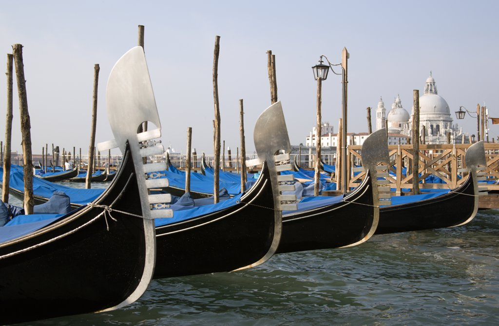 Stock Photo: 1850-20422 Italy, Veneto, Venice, Ferros Or Bows Of Gondolas Moored In The Molo San Marco Basin With The Baroque Church Of Santa Maria Della Salute On The Grand Canal In The Distance