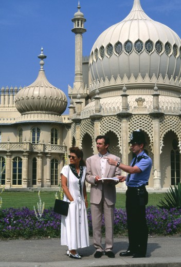 England, East Sussex, Brighton, Policeman Giving Tourist Couple Directions Outside The Royal Pavilion. : Stock Photo