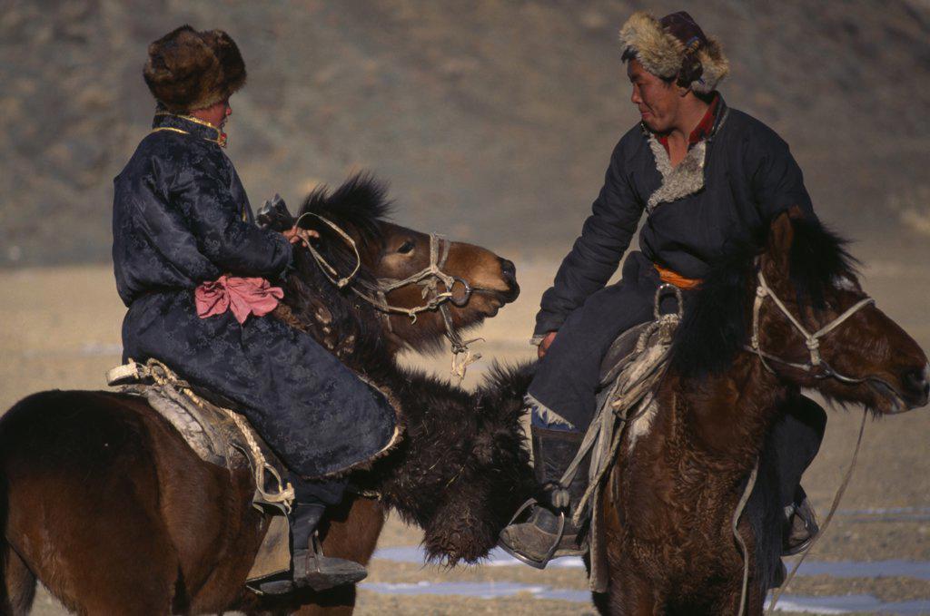 Stock Photo: 1850-20713 Mongolia, Bayan Olgi Province, Nomads, Kazakh Nomads Playing Bozkashi At Kazakh New Year Festival.  Two Riders Holding Headless Animal Carcass Between Them.