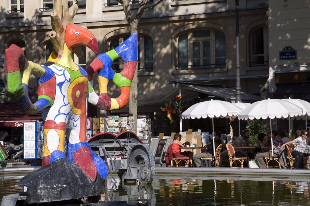 France, Ile De France, Paris, People Sitting At Tables Under Umbrellas Beside The Colourful Contemporary Fountains By Niki De Saint Phalle And Jean Tinguely In Place Igor Stravinsky Beside The Pompidou Centre In Beauborg Les Halles : Stock Photo