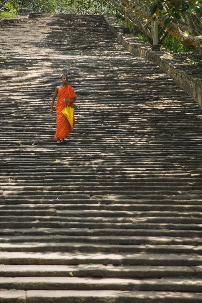 Stock Photo: 1850-21338 Sri Lanka, Mihintale, 'A Lone Monk Descending The Stairway, 1840 Granite Steps That Lead Up To The Dagobas And Shrines At The Top Of The Hill.'
