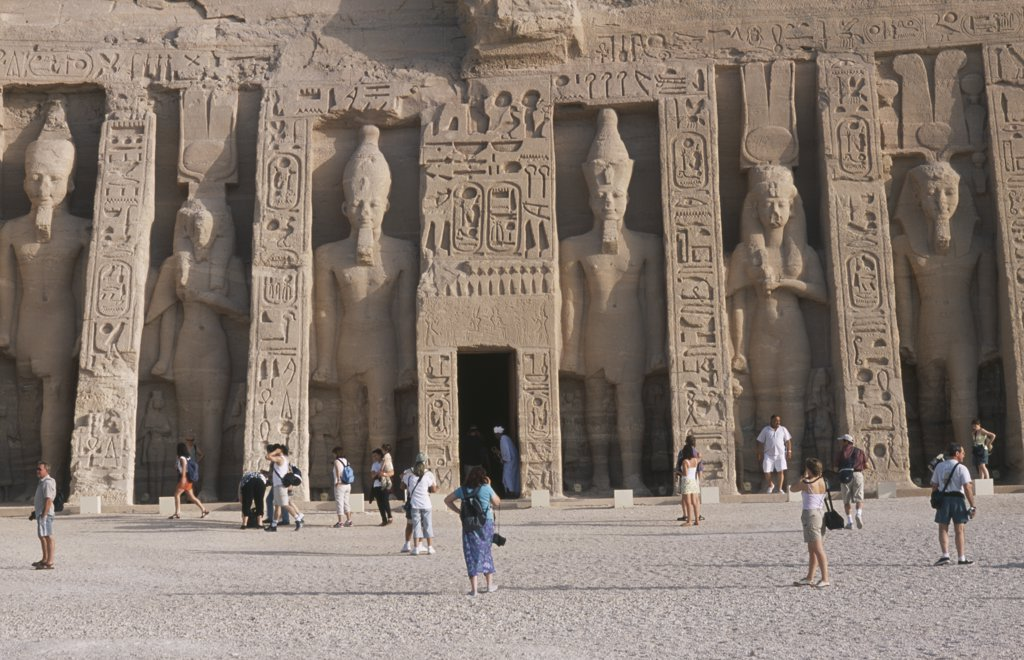 Stock Photo: 1850-21501 Egypt, Nile Valley, Abu Simbel, Hathor Temple . Built For Ramses Ii'S Wife Nefertari. Six Standing Statues Caved Into Facade. Visitors Walking In The Grounds.