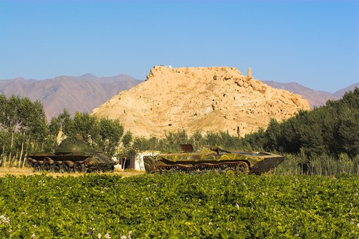 Afghanistan, Bamiyan Province, Bamiyan, 'Abandoned Tanks In Fied In Front Of Ruined Citadel Of Shahr-E-Gholgola Known As City Of The Screaming : Stock Photo
