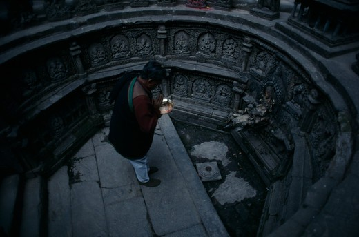 Stock Photo: 1850-21949 Nepal, Kathmandu, 'Man Worshipping In Sunken Tank And Former Royal Bath Known As Tusha Hiti In Sundari Chowk, Mangal Bazar.  Originally Built C. 1670 And Restored 1960.'