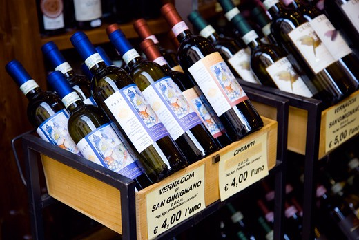 Stock Photo: 1850-23090 Italy, Tuscany, San Gimignano, Bottles Of Chianti And Vernaccia Di San Gimignano Wines Displayed For Sale Outside A Shop With Prices Given In Euros