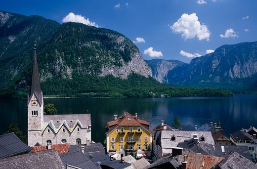 Austria, Oberosterreich, Hallstatt, 'View Over Tiled Village Rooftops, Hotel And Church With Lake And Mountains Behind.' : Stock Photo