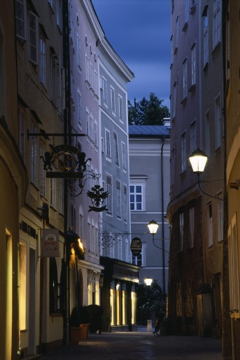 Austria, Salzburg, 'Narrow Street Of Judengasse At Night Lined By Tall, Grey, Pink And Cream Painted Buildings With Street Lamps Extending From Walls On Metal Brackets.' : Stock Photo