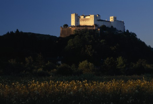Austria, Salzburg, Hohensalzburg Fortress Situated On Densely Wooded Hillside With Meadows Below.  Construction Started 1077 By Archbishop Gebhard. : Stock Photo