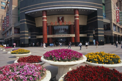 China, Beijing, Raised Circular Flower Beds Outside Sun Dong An Plaza Shopping Mall Entrance On Wangfujing Street. : Stock Photo