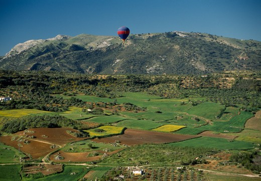 Spain, Andalucia, Malaga , A Hot Air Balloon Flying Over Green Valley With Patchwork Fields Towards Mountain Range : Stock Photo