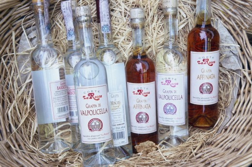 Italy, Veneto, Lake Garda, Bardolino.  Selection Of Bottles Of Grappa Displayed In Basket. : Stock Photo