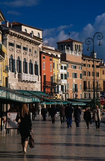Italy, Veneto, Verona, Piazza Bra.  People Walking Past Line Of Bars And Cafes And Painted Facades Of Architecture Overlooking Square. : Stock Photo