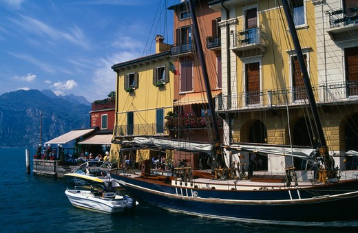 Italy, Veneto, Malcesine, 'Yellow, White And Terracotta Painted Facades Of Waterside Buildings With Moored Yacht And Motor Boats In Foreground.  People At Cafe At End Looking Out Across Lake ' : Stock Photo