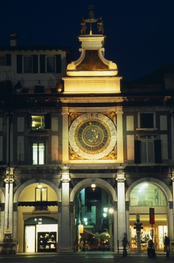 Italy, Lombardy, Brescia, 'Astronomical Clock In Piazza Della Loggia Illuminated At Night With Brightly Lit Shop Windows Framed By Archways Of Colonnade Below.  People, Street Lamps And Light Trail.' : Stock Photo