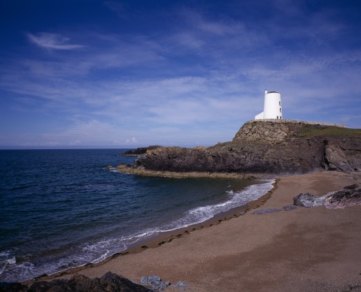 Stock Photo: 1850-24476 Wales, Isle Of Anglesey, Llanddwyn Island, 'Curving, Empty Beach Overlooked By Old Lighthouse Standing On Rocks Extending Out To Sea.  Blue Sky And Windswept Clouds Above.'