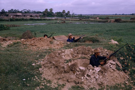 Vietnam, War, 'North Vietnamese Combat Troops, Positioned With Rifles And Machine Gun In Dug-Outs With Paddy Fields And Workers Behind.' : Stock Photo
