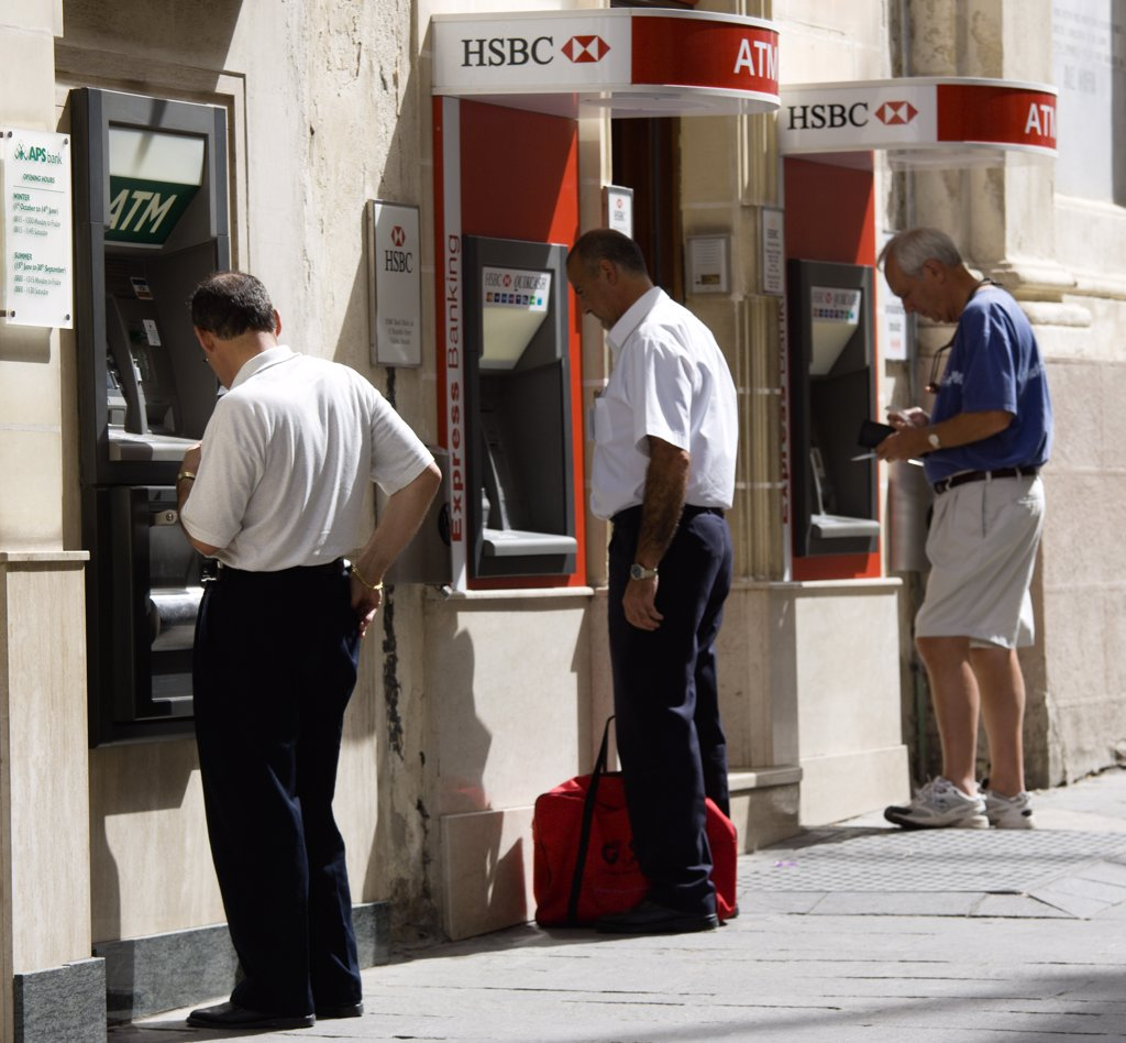 Stock Photo: 1850-24874 Malta, Valletta, Three Men Using Separate Atm Cash Machines On Republic Street