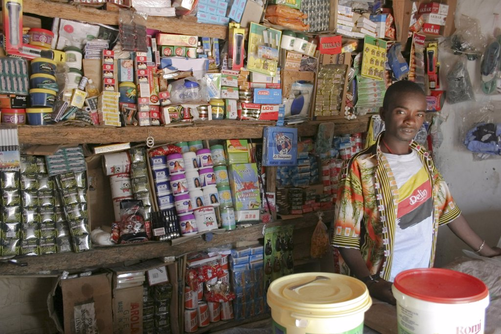 Gambia, Western Gambia, Tanji, 'Tanji Village.  Young, Male Owner Of A Grocery Shop Standing Behind Wooden Counter In Front Of Shelves With Display Of Various Products. ' : Stock Photo