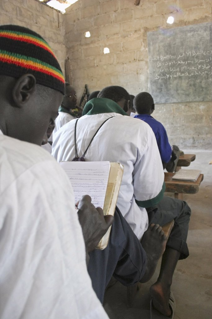 Gambia, Western Gambia, Tanji, Tanji Village.  Muslim Boys Writing In Arabic At Their Desks While Attending An Islamic Religious Class At The Ousman Bun Afan Islamic School.  Blackboard On Wall In Front Of Them. : Stock Photo