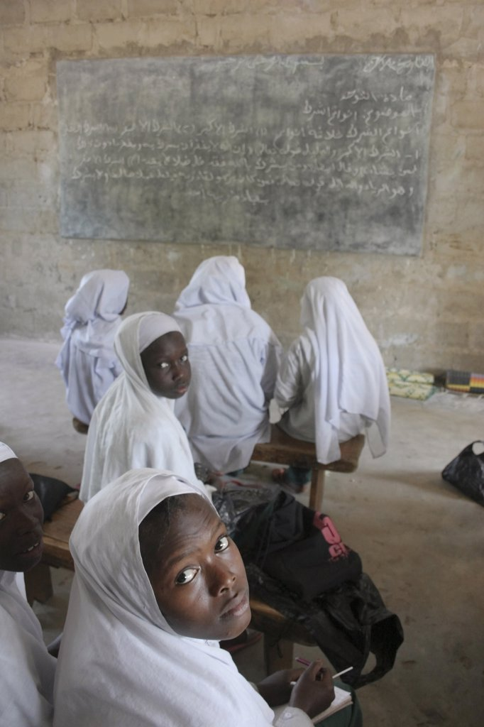 Stock Photo: 1850-25215 Gambia, Western Gambia, Tanji, Tanji Village.  African Muslim Girls Wearing White Headscarves Attending A Class At The Ousman Bun Afan Islamic School.  Girls In Foreground Looking Back Towards The Camera.