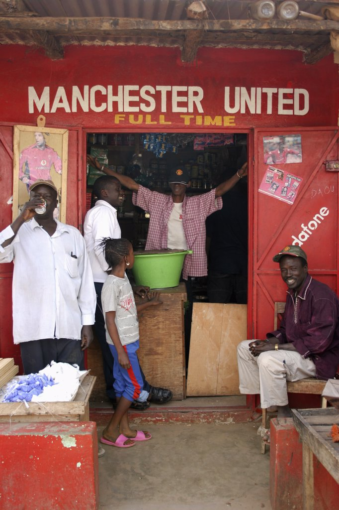 Stock Photo: 1850-25219 Gambia, Atlantic Coast, Banjul, 'Shop In Gambia'S Capital Banjul Painted Red And White, The Colours Of The Manchester United Football Strip And Decorated With Slogans And Posters With Group Of African Supporters Of The Team Gathered Outside And In Doorway.'