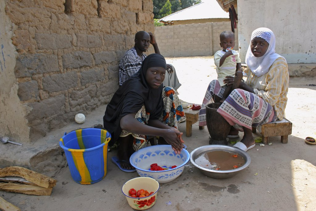 Stock Photo: 1850-25222 Gambia, Western Gambia, Tanji, Man Sitting In Shade In Yard Outside His House In The Company Of Two Of His Wives Who Are Taking Care Of A Child While Washing And Smashing Tomatoes To Be Used In The Family'S Meal