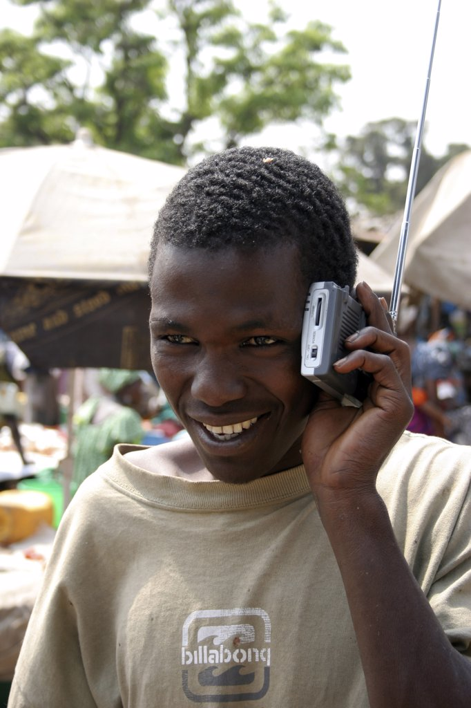 Stock Photo: 1850-25225 Gambia, Atlantic Coast, Banjul, 'Albert Market, Russell Street.  Young African Man Smiling  While Listening To A Radio Which He Is Holding Next To His Ear.'
