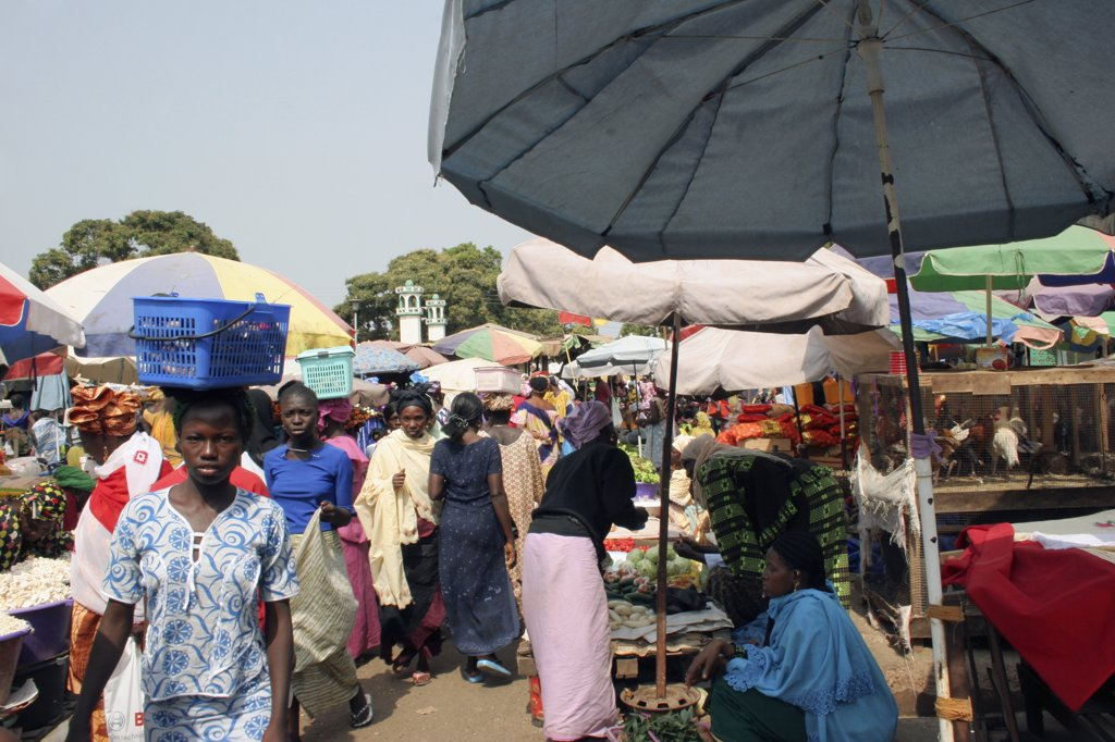 Gambia, Western Gambia, Serekunda, 'Bakau Market, Atlantic Road.  Busy Market Scene With Women Selling Fruit And Vegetables.  Woman In Foreground Carrying Box On Her Head.' : Stock Photo