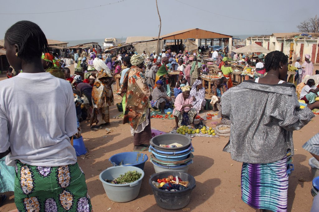 Gambia, Western Gambia, Tanji, Busy Market Scene With Women Selling Fruit And Vegetables And Coloufully Dressed Crowd. : Stock Photo