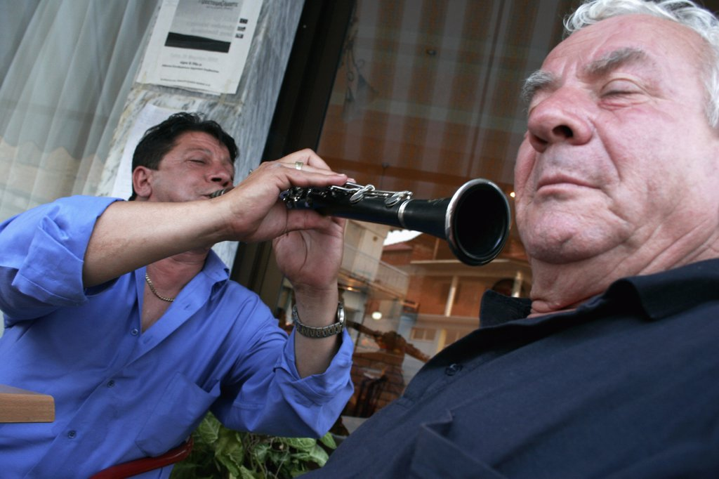 Greece, Macedonia, Kilkis, 'Toumba.  Street Musician Playing Clarinet, Perspective And Angle Of Picture Giving Appearance That He Is Directing Instrument And Sound Towards Ear Of Elderly Man In Foreground. ' : Stock Photo