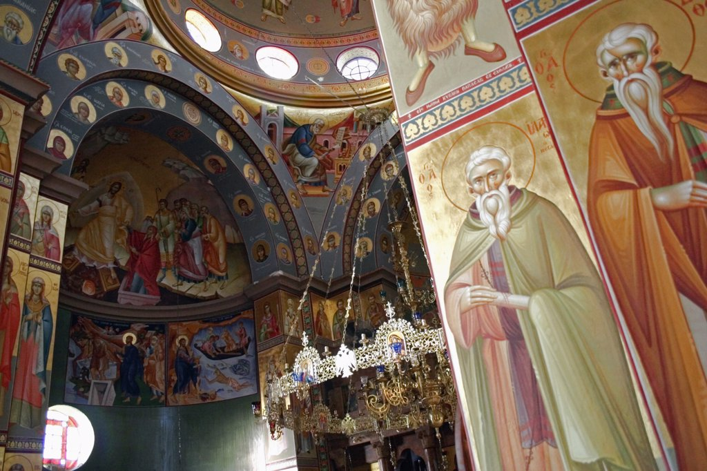 Stock Photo: 1850-25262 Israel, Hazafon, Sea Of Galilee, 'Nazareth.  Interior Of The Greek Orthodox Church Of St. Gabriel Also Known As The Church Of The Annunciation, Part View Of Domed Roof And Archways Decorated With Paintings Of Biblical Scenes And The Saints, Wall Hangings And Tiled Mosaics.  Church Is Located Over The Spring That Fed Marys Well.'