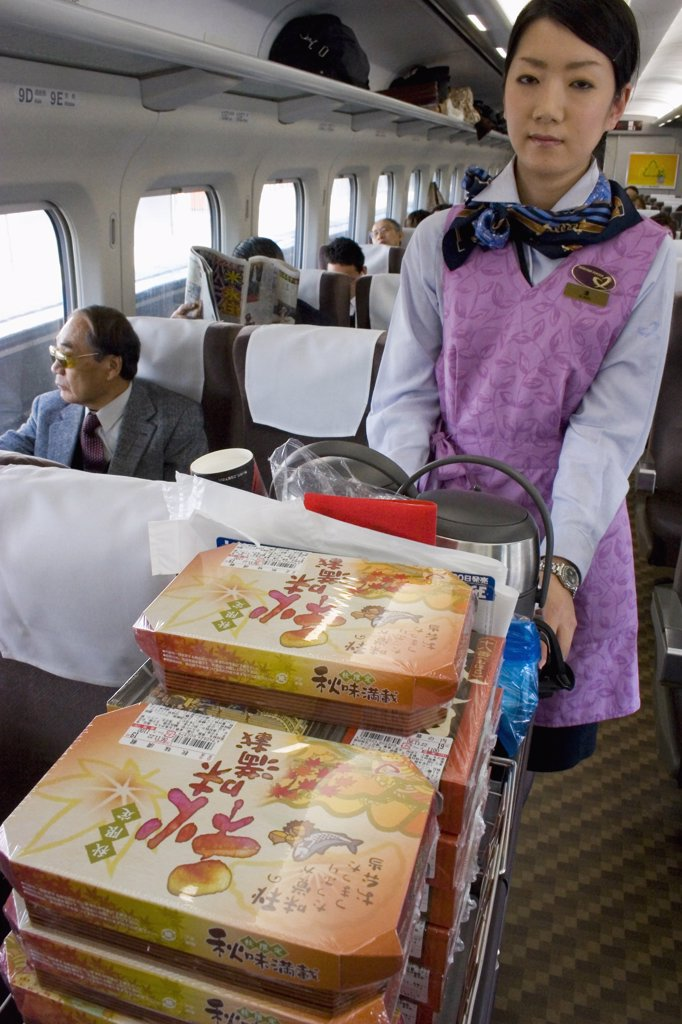 Stock Photo: 1850-25308 Japan, Honshu, 'Shinkansen Train Series 700, The ?Bullet Train? Travelling Between Tokyo And Kyoto.  Train Hostess Serving Bento Lunchboxes And Refreshments From Trolley. '