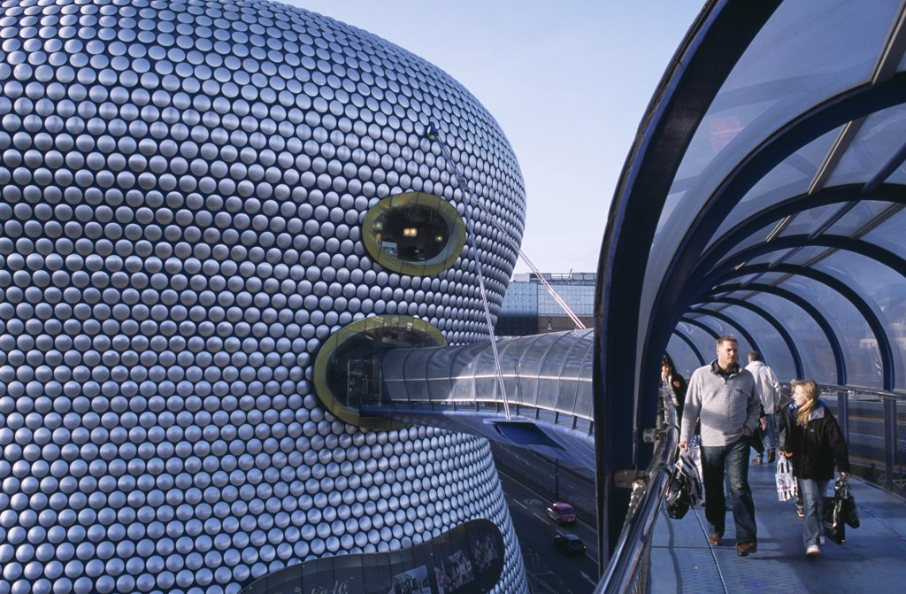 Stock Photo: 1850-26670 England, West Midlands, Birmingham, 'Selfridges Store At The Bullring Shopping Centre. Exterior Detail Of The Spun Aluminium Discs And Shoppers Walking Through The Parametric Bridge, A Curved Covered Footbridge Suspended Over The Street.'