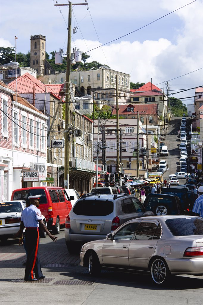 West Indies, Grenada, St George, Male Corporal Of The Royal Grenadian Police Force Directs Traffic In Busy Market Street In The Capital City Of St George'S : Stock Photo