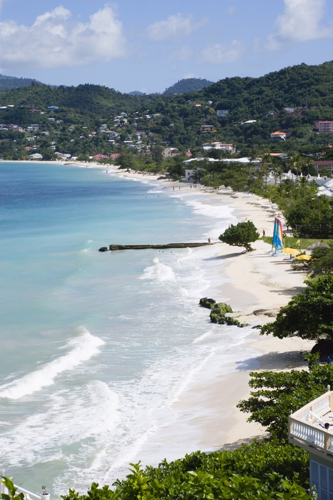West Indies, Grenada, St George, Waves Of The Aquamarine Sea Breaking On The Two Mile Stretch Of Grand Anse Beach With People On The White Sandy Beach : Stock Photo