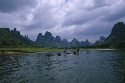 Stock Photo: 1850-2712 China, Guangxi, Guilin, Cormorant Fishermen On Rafts On The River Li With Limestone Karst Mountains In The Distance