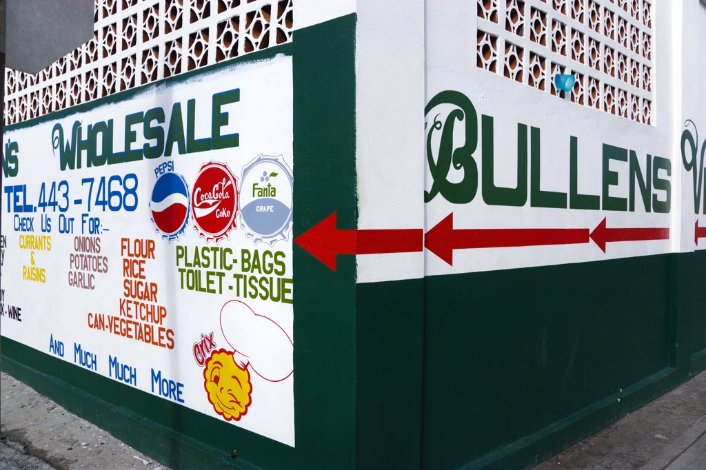 Stock Photo: 1850-27256 West Indies, Grenada, Carriacou, Hillsborough The Freshly Painted Walls Of Bullens Wholesale Shop Advertising Food And Drink And Household Goods.