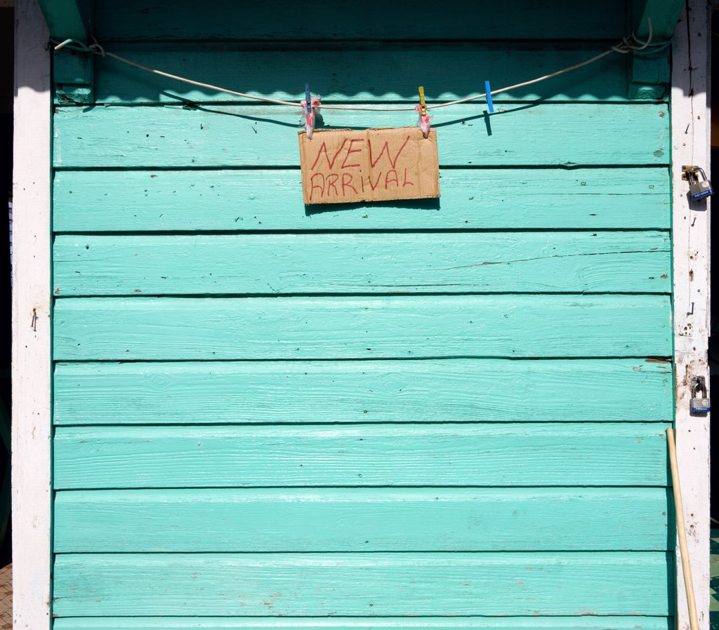 West Indies, Grenada, Carriacou, New Arrival Sign On The Padlocked Turqoise Shutter Of A Shop In Hillsborough. : Stock Photo