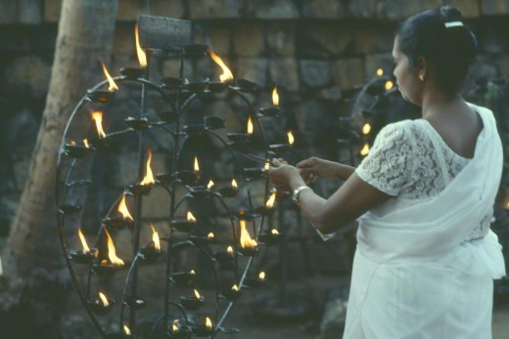 Stock Photo: 1850-273 Sri Lanka, Anuradhapura, Lighting Lamp Beside Bo Tree During Wesak Festival.