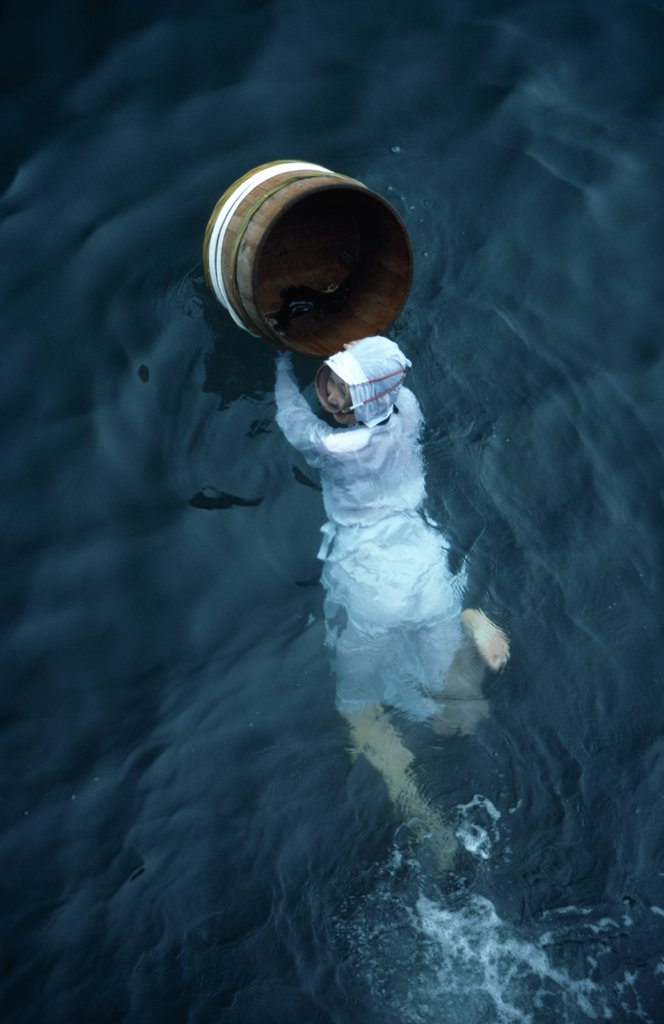 Stock Photo: 1850-28556 Japan, Honshu, Toba, Traditional Female Pearl Diver Swimming In The Water With Wooden Barrel For Collecting Oysters At The Mikimoto Pearl Farm In Mie Prefecture In Kansai Region.