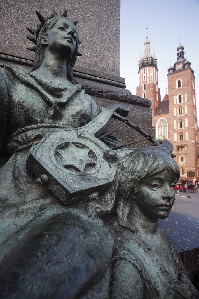 Stock Photo: 1850-28828 Poland, Krakow, Stare Miasto  Rynek Glowny.  Detail Of Memorial Statue Of The Romantic Poet Adam Mickiewicz Designed By Teodor Rygier In 1898.  Allegorical Female Figure Representative Of The Muse Of Poetry On South Side Of Pedestal Base.  St Mary S Church Behind.