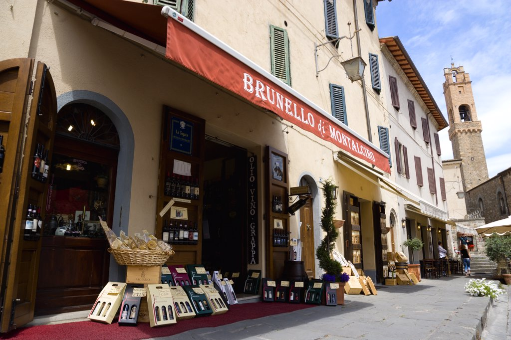Stock Photo: 1850-29140 Italy, Tuscany, Montalcino, Val Dorcia Brunello Di Montalcino Enoteca Or Wine Shop With Display Of Boxed Wines On The Pavement Around Its Entrance Beneath A Sunshade. The 14 The Century Belltower Of The Palazzo Comunale Is At The End Of The Street.