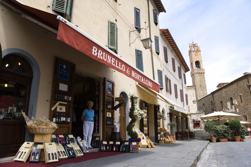 Stock Photo: 1850-29146 Italy, Tuscany, Montalcino, Val Dorcia Brunello Di Montalcino Enoteca Or Wine Shop With Display Of Boxed Wines On The Pavement Around Its Entrance Beneath A Sunshade. The 14 The Century Belltower Of The Palazzo Comunale Is At The End Of The Street.